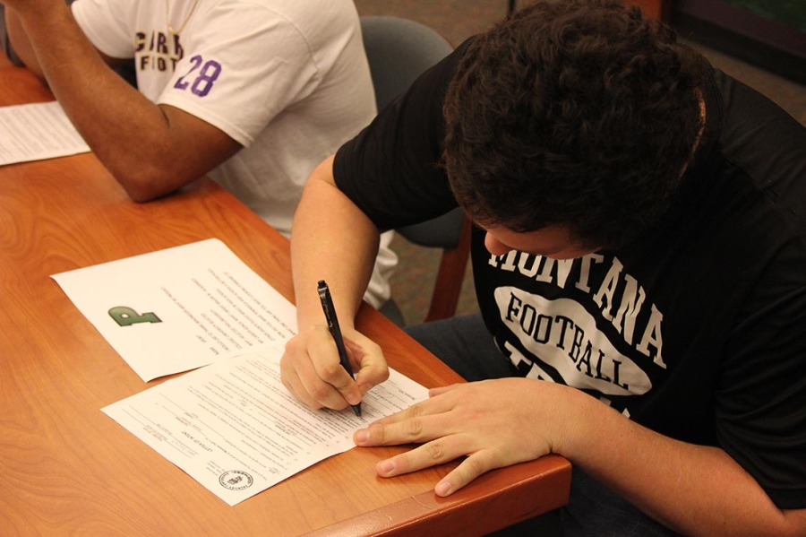 Football player Hayden Smith signing letter of intent to Montana Tech.