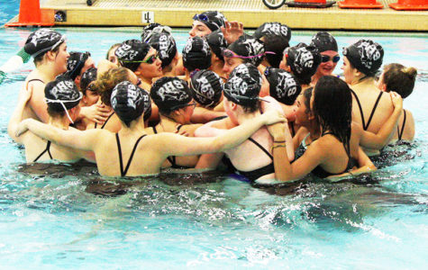 PHS Girls Swim team huddled together before a meet.