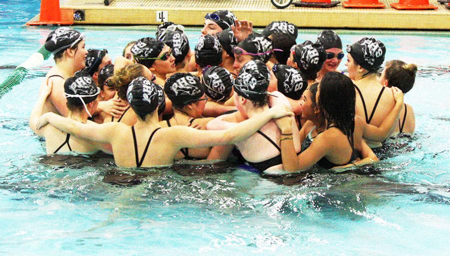 PHS Girls Swim team huddled together before a meet.