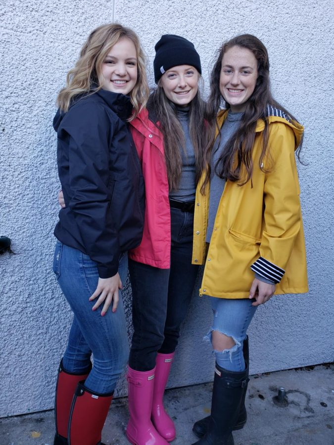 Elyse Donley, Julia Klumker, and Maeve Griffin show off their rain gear for Rainy Day