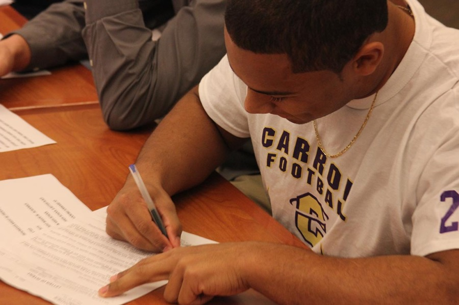 Football player Major Ali signing letter of intent to Carroll College.