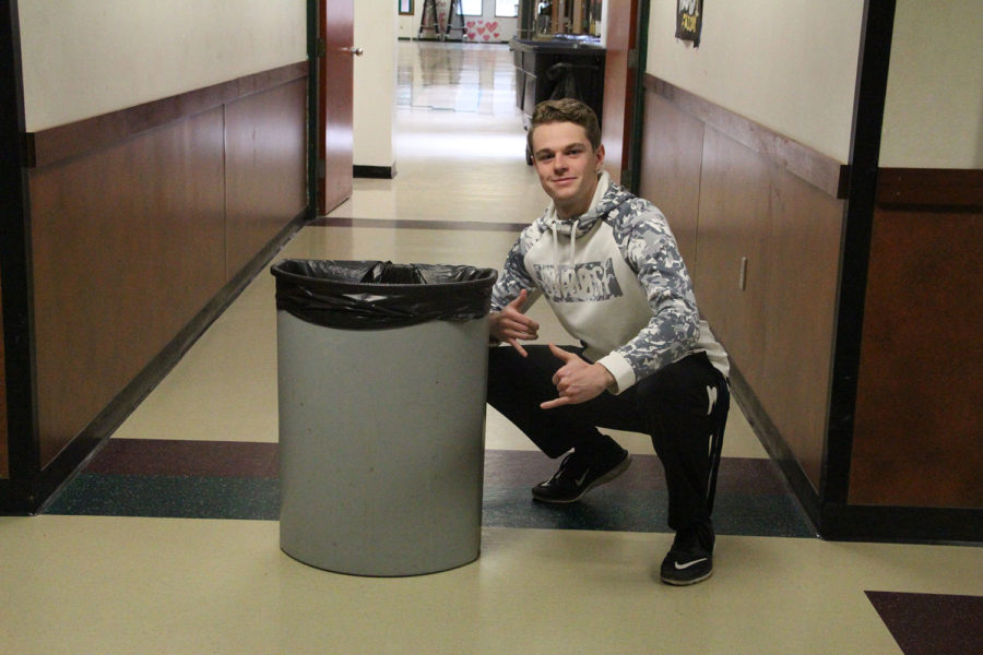 Ian Collins casually poses next to a garbage can.